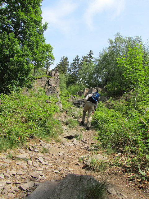 Easy Hiker clambering on a steep and stony trail in the Saar-Huensrucksteig in Germany""