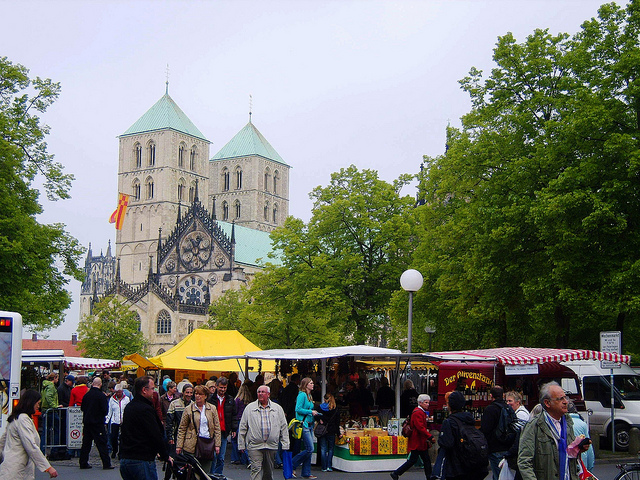 """The weekly town market in Muenster in the shadows of its cathedral"""