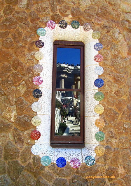 """Visitors to Park Güell in Barcelona reflected on a window of the ticketing office of the park"""