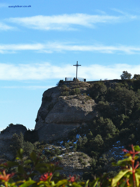 """A giant cross high above the Montserrat rocks near Barcelona"""