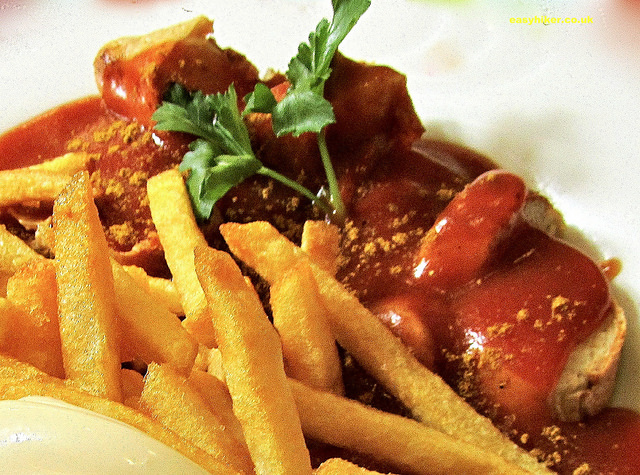 """Sliced German Currywurst - Bratwurst bathed in Curry sauce with a side dish of french fries"""