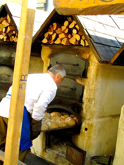 """bread being baked in a wood fired oven in one of the wine festivals in Speyer in Germany"""