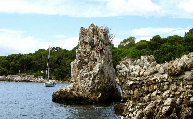 """A boy climbing the rocks by Cap d'Antibes"""
