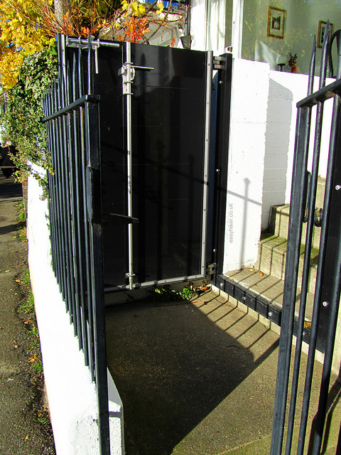 """heavy metal gate in front of a door of an apartment along the Thames"""