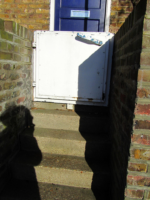 """Closed heavy metal gate in front of a door of an apartment along the Thames"""