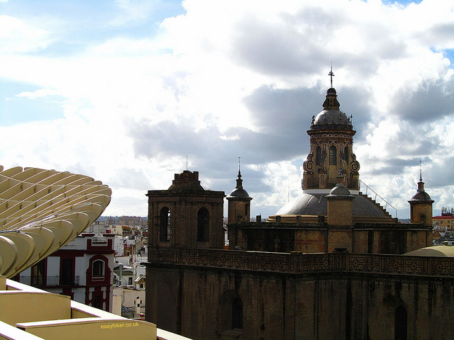 """A baroque church tower seen from the Mirasol Parasol building in Sevilla"""