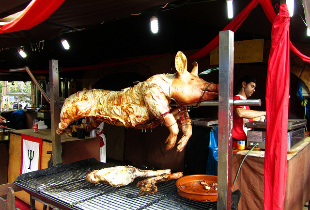 """A whole roast pig on a spit in a food fair in Seville"""