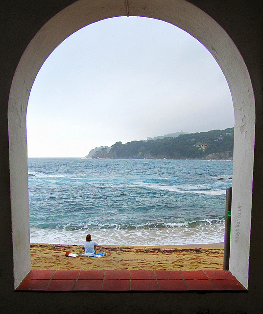 """woman contemplating the sea framed by an arch in the fishing village in Palafrugell"""