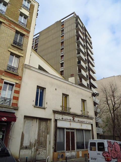 """old building in the shadow of new tenement housing buildings in the Belleville of Edith Piaf in Paris"""