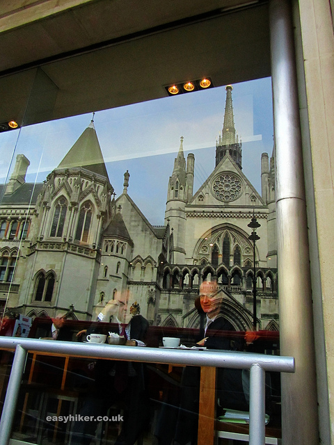 """The Royal Courts of Justice along the London crime trail reflected on cafe front"""