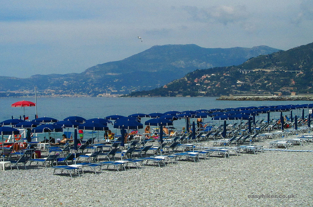 """Beach chairs and parasols along beach in Ventimiglia towards Bordighera"""