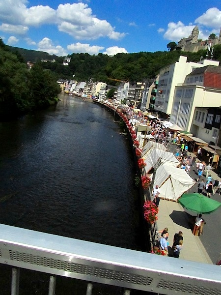 """The bank of the river Lenne in Altena Germany occupied by stalls for an annual fair"""
