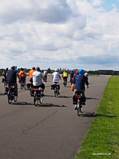 """A group of cyclists on a runway of the Tempelhof airport in Berlin"""