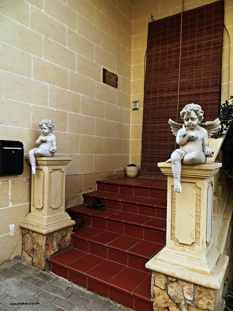 """statues of cherubs in front of a house in Gozo"""
