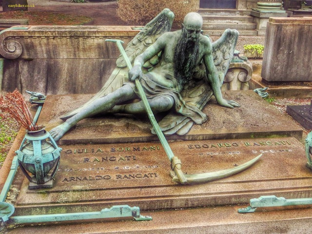 """statue of the grim reaper on a tomb in Cimitero Monumentale in Milan"""