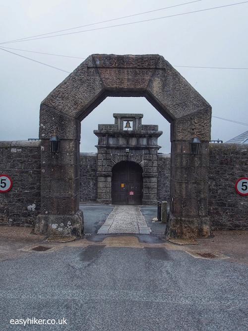 """entrance gate of Dartmoor Prison on a bleak landscape in Dartmoor"""