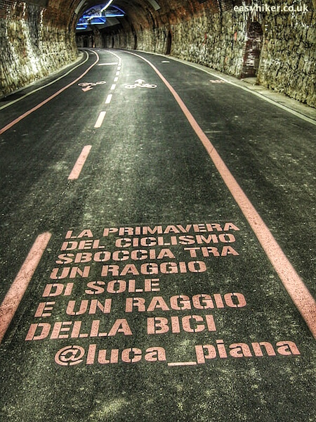 """an italian quote on the asphalted road of old railway tunnel Ospedaletti-Sanremo"""